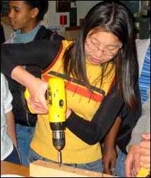 Girl holding power drill with both hands